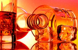 Whiskey Bottle & Glasses Abstract. Bottle and glasses of whiskey against multi colored abstract background Royalty Free Stock Photography