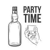 Whiskey bottle and hand holding full shot glass Royalty Free Stock Photo