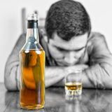 Whiskey bottle with an out of focus drunk man Royalty Free Stock Photography