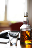 Whiskey bottle on the table. Bottle of alcoholic drink with an empty glass on a table Stock Images