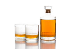 Whiskey bottle with two glasses of whiskey in white background Royalty Free Stock Images