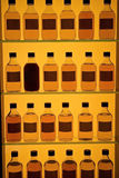 Whiskey bottles. In row at the cabinet Stock Photos