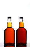 Whiskey bottles. Two full and closed glass bottles of Scotch Whiskey isolated on white studio background Royalty Free Stock Image