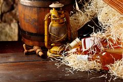 Whiskey bottles. Posterous, inverted vintage whiskey wooden containers box, kerosene lantern style oil lamps, wooden barrel. Still. Life. Copy space royalty free stock images