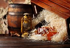 Whiskey bottles. Posterous, inverted vintage whiskey wooden containers box, kerosene lantern style oil lamps, wooden barrel. Still. Life. Copy space royalty free stock photos