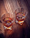 Whiskey, bourbon, brandy, or cognac on log table. Strog alcohol in the glass Royalty Free Stock Image