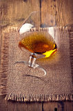 Whiskey, bourbon, brandy, or cognac on log table. Strong alcohol in the glass Royalty Free Stock Photos