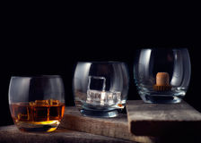 Whiskey, bourbon, brandy, or cognac on log table. Strong alcohol in the glass Stock Photos