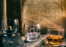 Whiskey, bourbon, brandy, or cognac on log table. Strong alcohol in the glass Royalty Free Stock Image