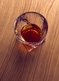 Whiskey, bourbon, brandy, or cognac on log table. Strong alcohol in te glass Stock Images