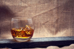 Whiskey, bourbon, brandy, or cognac on log table. Strong alcohol in te glass Stock Image