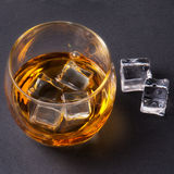Whiskey, bourbon, brandy, or cognac on log table. Strong alcohol in te glass Stock Photos