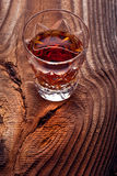 Whiskey, bourbon, brandy, or cognac on log table. Strong alcohol in te glass Royalty Free Stock Photos