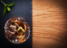 Whiskey, bourbon, brandy, or cognac on log table. Strong alcohol in te glass Stock Photography