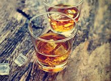 Whiskey bourbon with ice on wooden texture background. Stock Photography