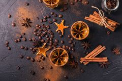 Whiskey, brandy or liquor, spices, anise stars, coffee beans, ci. Whiskey, brandy or liquor, coffee beans, spices and decorations on dark background. Seasonal Royalty Free Stock Photo