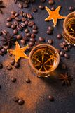 Whiskey, brandy or liquor, spices, anise stars, coffee beans, ci. Whiskey, brandy or liquor, coffee beans, spices and decorations on dark background. Seasonal Stock Image