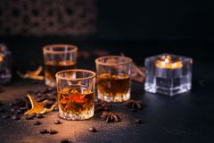 Whiskey, brandy or liquor, spices, anise stars, coffee beans, ci. Whiskey, brandy or liquor, coffee beans, spices and decorations on dark background. Seasonal Stock Photography