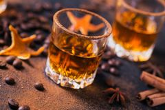Whiskey, brandy or liquor, spices, anise stars, coffee beans, ci. Whiskey, brandy or liquor, coffee beans, spices and decorations on dark background. Seasonal Stock Photo