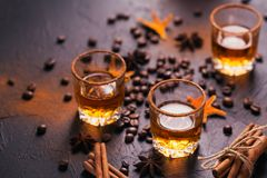 Whiskey, brandy or liquor, spices, anise stars, coffee beans, ci. Whiskey, brandy or liquor, coffee beans, spices and decorations on dark background. Seasonal Royalty Free Stock Image