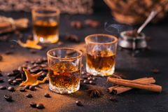 Whiskey, brandy or liquor, spices, anise stars, coffee beans, ci. Whiskey, brandy or liquor, coffee beans, spices and decorations on dark background. Seasonal Royalty Free Stock Photos