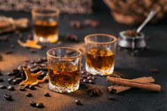 Whiskey, brandy or liquor, spices, anise stars, coffee beans, ci. Whiskey, brandy or liquor, coffee beans, spices and decorations on dark background. Seasonal Stock Photos
