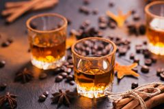 Whiskey, brandy or liquor, spices, anise stars, coffee beans, ci. Whiskey, brandy or liquor, coffee beans, spices and decorations on dark background. Seasonal Royalty Free Stock Images
