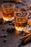 Whiskey, brandy or liquor, spices, anise stars, coffee beans, ci. Whiskey, brandy or liquor, coffee beans, spices and decorations on dark background. Seasonal Royalty Free Stock Photography