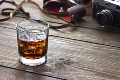 Whiskey and camera. Whiskey with ice on a table near the camera Royalty Free Stock Photo
