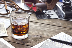 Whiskey and camera. Whiskey with ice on a table near the camera Stock Photo