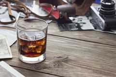 Whiskey with a camera. On a wooden table Royalty Free Stock Photos