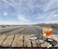 Whiskey with car keys and handcuffs royalty free stock photography