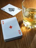 Whiskey and cards. Whiskey drink by two ace playing cards on wooden table Royalty Free Stock Photos