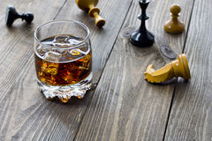 Whiskey and chess. Whiskey on a table with scattered through chess Stock Photos