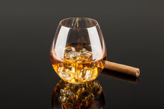 Whiskey & Cigar. A glass of whiskey on the rocks and a cigar  on dark background Royalty Free Stock Photos