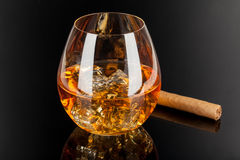 Whiskey & Cigar. A glass of whiskey on the rocks and a cigar  on dark background Stock Images