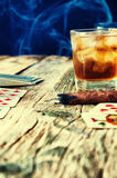 Whiskey, cigar and cards on a wooden background Stock Photos