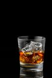 Whiskey. Close up of glass of whiskey over a black background Royalty Free Stock Image