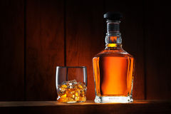 Whiskey. Close up view of glass with ice and whiskey and a bottle aside royalty free stock photos