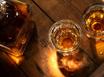 Whiskey. Close up view of nice bottle and two glasses filled with whiskey royalty free stock photo