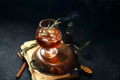 Whiskey cocktail with ice and burnt rosemary. Dark background, vintage papers, dramatic ligting. Horizontal composition with copy space Stock Image