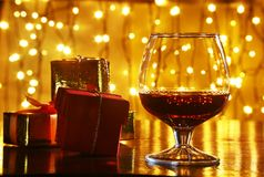 Whiskey, cognac, brandy and gift box on wooden table. Celebration composition on the light background. Royalty Free Stock Photography