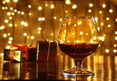 Whiskey, cognac, brandy and gift box on wooden table. Celebration composition on the light background. Royalty Free Stock Images