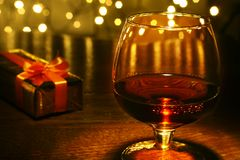 Whiskey, cognac, brandy and gift box on wooden table. Celebration composition on the light background. Stock Photography