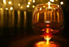 Whiskey, cognac, brandy and gift box on wooden table. Celebration composition on the light background. Stock Images
