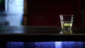 Whiskey con ghiaccio su una tavola di legno HD sparato con il cursore video d archivio