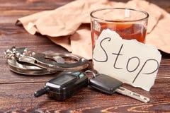 Whiskey con le chiavi e le manette dell'automobile fotografie stock