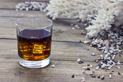 Whiskey and Coral. Among the rocks on the wooden table Stock Photography