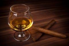 Whiskey dans le verre ballon avec des cigares Image stock