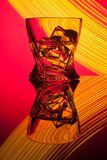 Whiskey de cocktail par verre avec de la glace de morceaux de la réflexion de partie un concept des effets de la lumière jaunes d photo stock